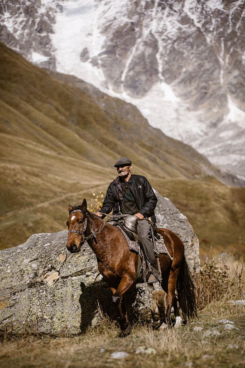 Gruzin na koniu pośród gór Svaneti w Ushguli